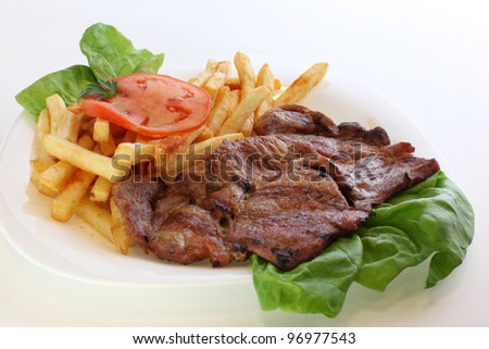 Juicy grilled pork chop (neck cut) with french fries - stock photo