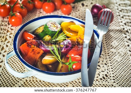 Juicy grilled vegetables in metal, rustic bowl on a wooden table.