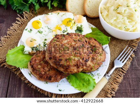 Juicy home cutlets (beef, pork, chicken) fried eggs and mashed potatoes on a wooden background. - stock photo
