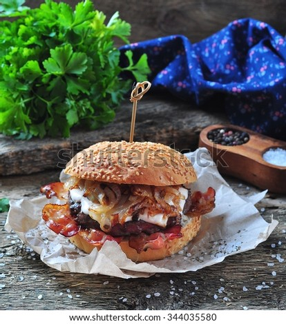 juicy homemade burger beef with fried onions on a wooden background - stock photo