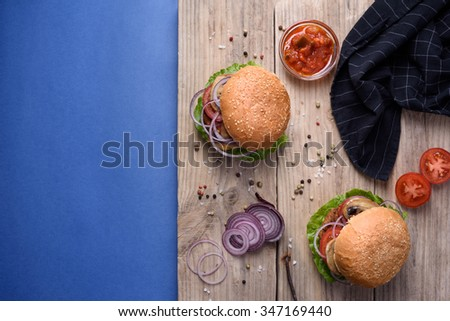 Juicy homemade burgers with sesame seeds, served with tomato sauce, pepper and sea salt on wooden board on blue background. Top view, copy space. - stock photo