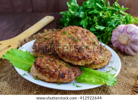 Juicy homemade cutlets (beef, pork, chicken) on a wooden background. For a hamburger. - stock photo