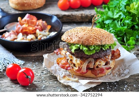 juicy homemade double burger beef with fried onions on a wooden background - stock photo