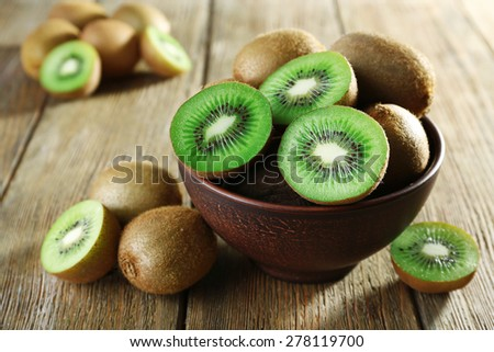 Juicy kiwi fruit in bowl on wooden background - stock photo