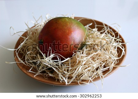 juicy mangoes stored on straw background