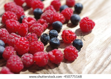 Juicy mature berries of  raspberry and bilberry  close up. Berry background - stock photo