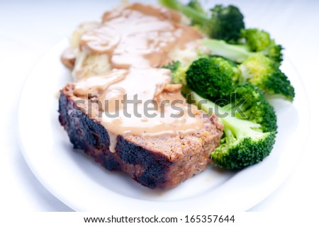 juicy meatloaf with mashed potatoes and vegetables smothered with a thick mushroom gravy - stock photo