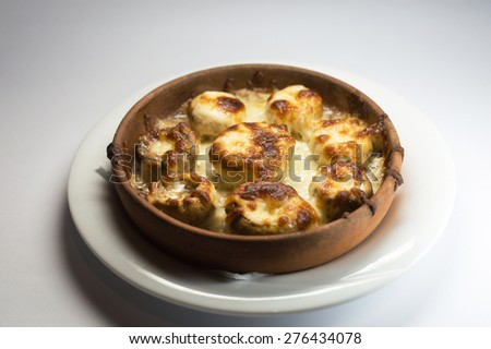 Juicy  Mushrooms baked with cheese in a clay dish - stock photo