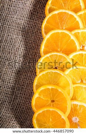 Juicy orange slices on jute bag - stock photo