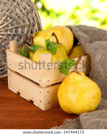 Juicy pears in wooden box on table on bright background