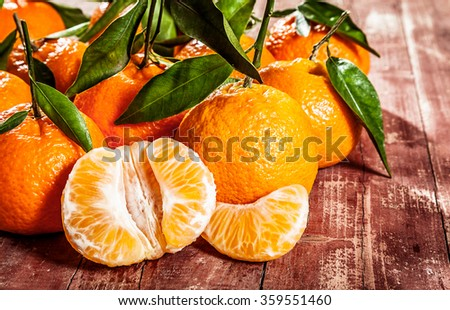 Juicy peeled segments of tangerine displayed on a rustic wooden table with whole fresh fruit with green leaves in a close up view - stock photo