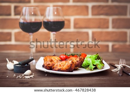 Juicy pieces of grilled meat fillet served with cherry tomatoes branch and lettuce on a white plate, glass of red wine, knife, fork, on the brick wall background. Romantic concept. Horizontal