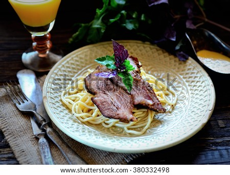 juicy pieces of meat on a plate with spaghetti, basil sauce, parsley - stock photo