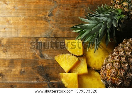 Juicy pineapple slices on wooden table - stock photo
