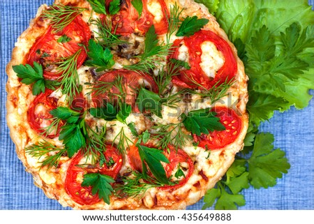 juicy pizza closeup lying on jeans tablecloth - stock photo