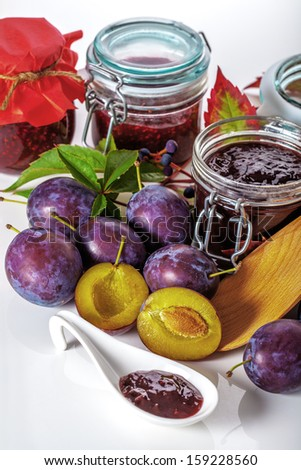 Juicy plums and opened jars with jams - stock photo