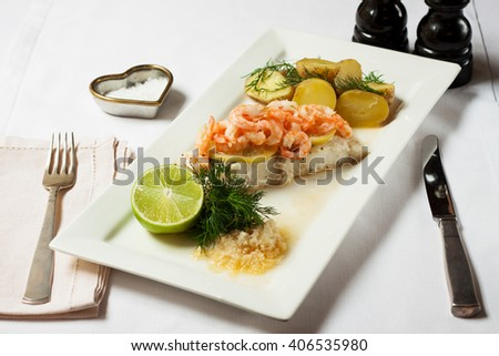 Juicy poached cod with shrimps and potatoes served with lime on white oblong plate - stock photo