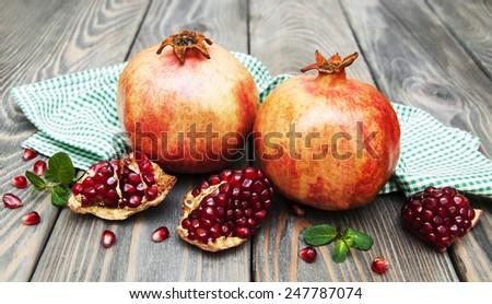 juicy pomegranates on a old wood background - stock photo