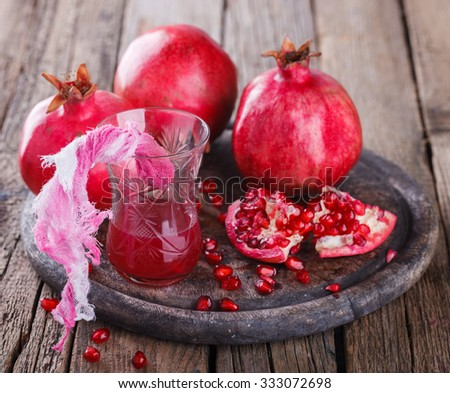 Juicy pomegranates,whole and broken and pomegranate juice on wooden background.selective focus.