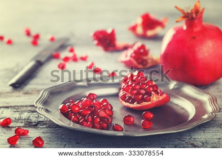 Juicy pomegranates,whole and broken vintage on a metal plate.Toned image. Vintage style selective focus. - stock photo