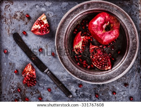 Juicy pomegranates,whole and broken vintagey on a metal plate.Toned image. Vintage styleselective focus. - stock photo