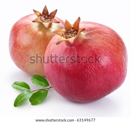 Juicy pomegranates with leaves. Isolated on a white background.