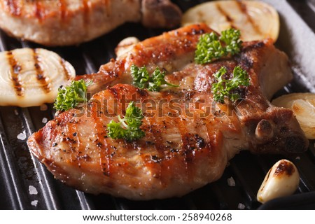 Juicy pork steak grilled with onions and garlic in a pan grill closeup. horizontal