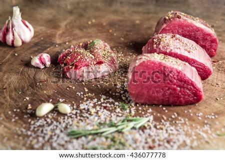 Juicy raw beef steak on wooden table - stock photo