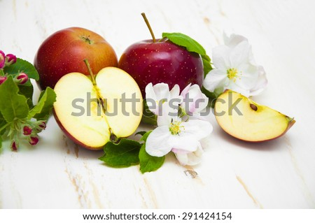 Juicy red apples and blossom on a white wooden background - stock photo