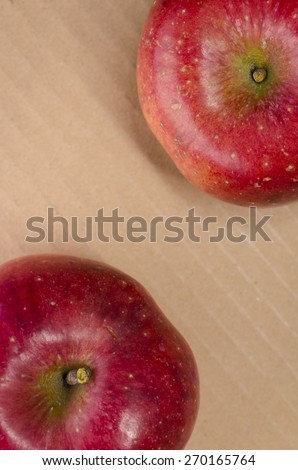 juicy red apples close up, light brown paperboard background - stock photo