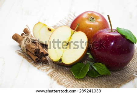 Juicy red apples with cinnamon on a white wooden background - stock photo