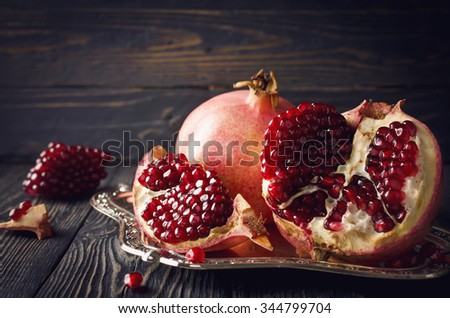 Juicy red pomegranate with seeds on wooden table - stock photo