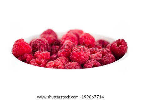 Juicy red raspberries in the white bowl isolated on white background - stock photo