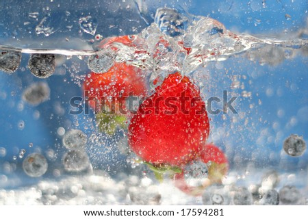 Juicy red strawberries and blueberries plunging into some sparkling water.  Shallow depth of field. - stock photo