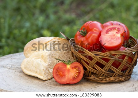juicy red tomatoes and bread in basket on wooden table