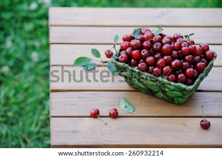 Juicy ripe cherries in a basket on wooden table outdoor - stock photo
