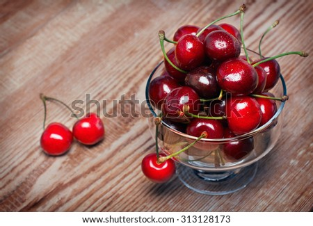 Juicy ripe cherries in a bowl of clear glass on old wooden table top.