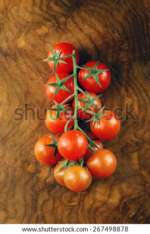 juicy ripe cherry tomatoes on a branch on a wooden background - stock photo