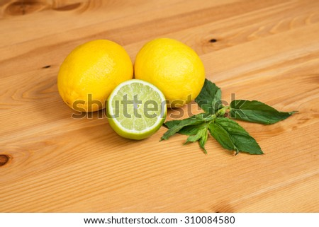 Juicy ripe citrus on a wooden table - lime, lemon and mint - stock photo