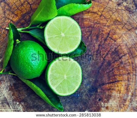Juicy ripe citrus on an old wooden table - lime, lemon - stock photo