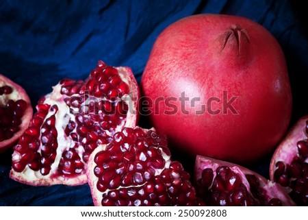 Juicy ripe pomegranates on dark blue background - stock photo