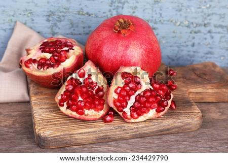 Juicy ripe pomegranates on old wooden table - stock photo