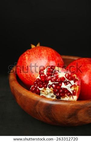 Juicy ripe pomegranates on wooden table, on dark background - stock photo
