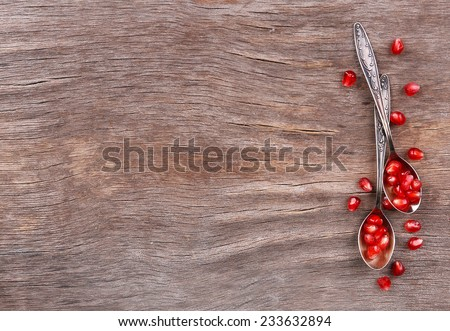 Juicy ripe pomegranates seeds in spoons, on old wooden table - stock photo