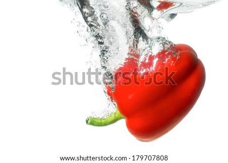 Juicy ripe red paprika with a nice splash falling into the clear water. Healthy natural vegetable food and vegetarian concept - stock photo