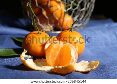 Juicy ripe tangerines with leaves on tablecloth - stock photo