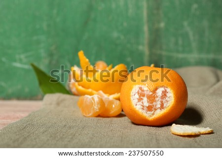 Juicy ripe tangerines with leaves on wooden background - stock photo