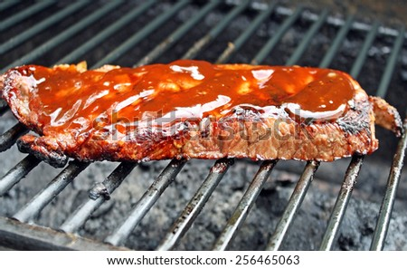 Juicy Sirloin Steak with Barbecue Sauce Cooking on The Grill