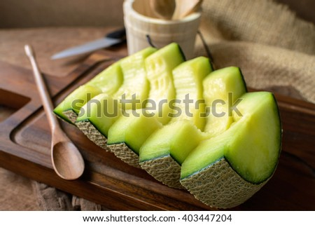 Juicy slice melon on rustic wooden table background. - stock photo