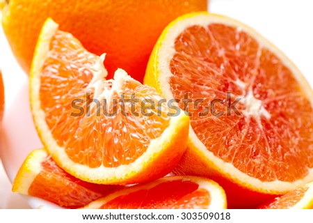 juicy sliced red oranges close-up on white plate  - stock photo